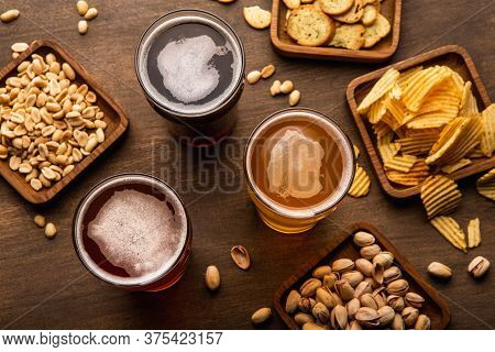 Different Types Of Beer And Snacks. Craft Drinks In Glasses And Pistachios, Nuts, Crackers, Crisps A