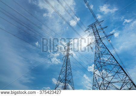 High Voltage Electric Pylon And Electrical Wire Against Blue Sky And White Clouds. Bottom View Of El
