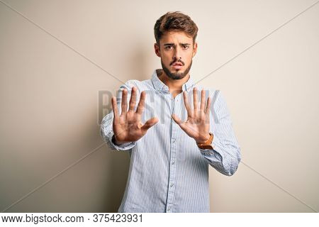 Young handsome man with beard wearing striped shirt standing over white background Moving away hands palms showing refusal and denial with afraid and disgusting expression. Stop and forbidden.