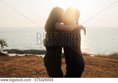Backlit Portrait Of A Young Romantic Couple Swirls In A Hug Against The Backdrop Of The Sea. Anjuna