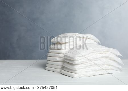 Baby Diapers On White Wooden Table Against Grey Background. Space For Text