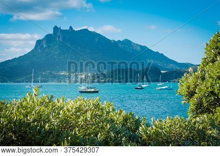 View Above Tree Branches Over Tranquil Azure Water Of The Bay And Mount Manaia