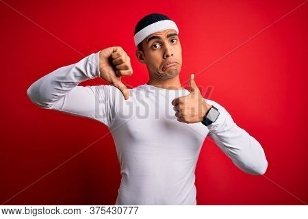 Young handsome african american sportsman wearing sportswear over red background Doing thumbs up and down, disagreement and agreement expression. Crazy conflict