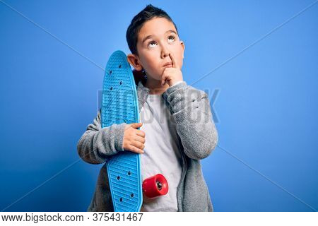 Young little boy kid skateboarder holding modern skateboard over blue isolated background serious face thinking about question, very confused idea