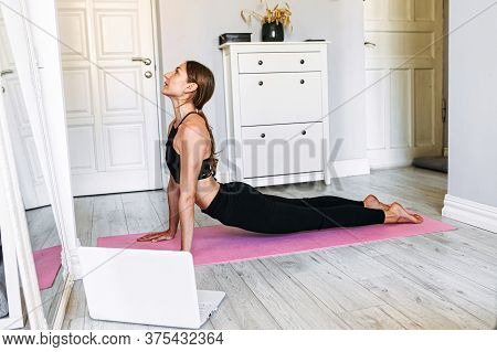 Stretching Workout At Home Using A Laptop. Beautiful Girl Is Stretching At Home After An Online Work