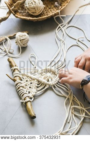 Female Hands Weave Macrame The Home Workshop. Boho Lifestyle. Hobby Hobby Concept. Selective Focus