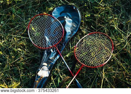 Two Crossed Badminton Racquets Laying On A Grass. Sport And Summer Outdoor Activities