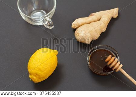 Health Remedy Relief Foods For Cold And Flu With Lemon, Ginger And Honey On A Black Background. Top
