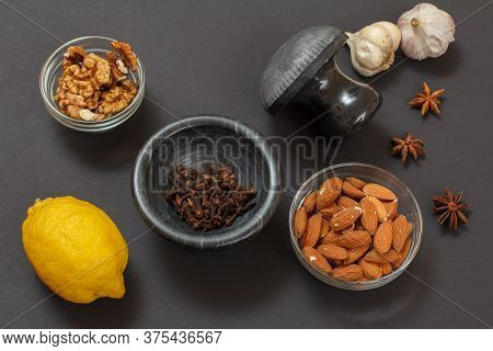 Health Remedy Foods For Cold And Flu Relief With Lemon, Garlic, Almond And Walnuts On A Black Backgr