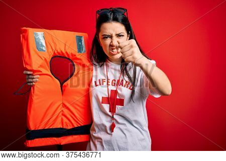 Young lifeguard woman holding rescue lifejacket over red background annoyed and frustrated shouting with anger, crazy and yelling with raised hand, anger concept
