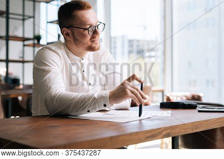 Thoughtful Young Man Wearing Fashion Casual Clothing And Stylish Eyeglasses Is Writing Text On Paper