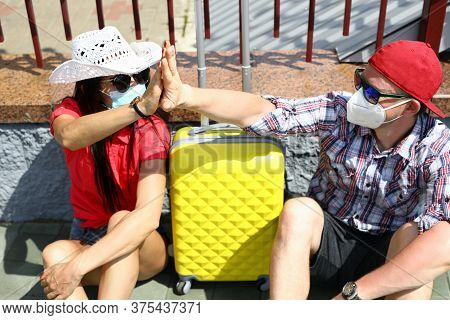 Man And Woman In Medical Masks With Suitcase Go On Trip. Covid 19 Travel 2020 Concept
