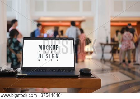 Mockup Blank White Screen Laptop With Blurred People Waiting For Registration In Hotel Hall