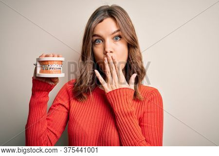 Young blonde girl holding orthodontist prosthesis denture over isolated background cover mouth with hand shocked with shame for mistake, expression of fear, scared in silence, secret concept