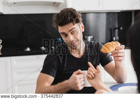 Selective Focus Of Woman Flirting With Boyfriend Holding Croissant And Cup Of Coffee In Kitchen