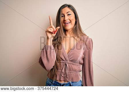 Young beautiful brunette elegant woman with long hair standing over isolated background showing and pointing up with finger number one while smiling confident and happy.