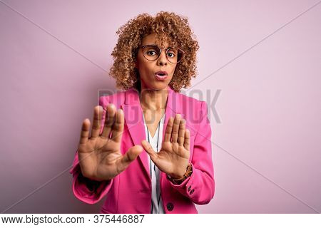 Young african american businesswoman wearing glasses standing over pink background Moving away hands palms showing refusal and denial with afraid and disgusting expression. Stop and forbidden.