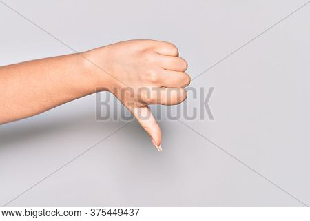 Hand of caucasian young woman doing thumbs down rejection gesture, disapproval dislike and negative sign