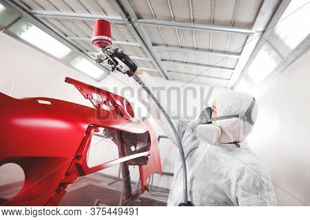 Auto Mechanic Worker Painting Car Element With Spray Gun In A Paint Chamber During Repair Work.