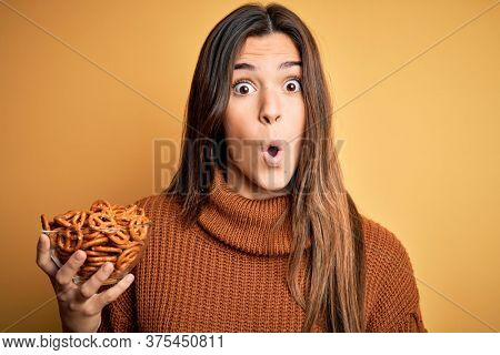 Young beautiful girl eating baked german pretzel standing over isolated yellow background scared in shock with a surprise face, afraid and excited with fear expression