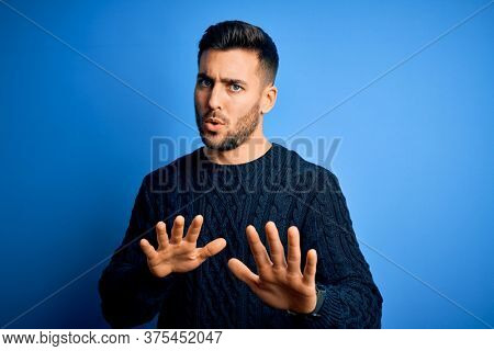 Young handsome man wearing casual sweater standing over isolated blue background Moving away hands palms showing refusal and denial with afraid and disgusting expression. Stop and forbidden.