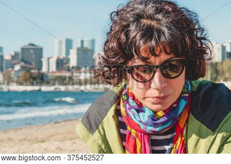 Outdoor Portrait Of Pretty Curly Woman With Colorful Clothings And Sunglasses, Sitting On The Beach