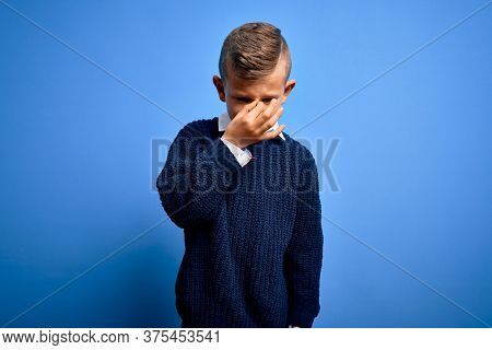 Young little caucasian kid with blue eyes wearing winter sweater over blue background tired rubbing nose and eyes feeling fatigue and headache. Stress and frustration concept.