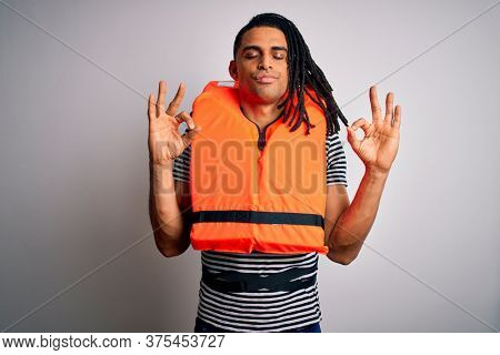 Young african american afro man with dreadlocks wearing orange lifejacket relax and smiling with eyes closed doing meditation gesture with fingers. Yoga concept.