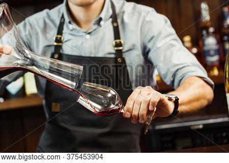 Sommelier Pouring Wine Into Glass From Mixing Bowl. Male Waiter