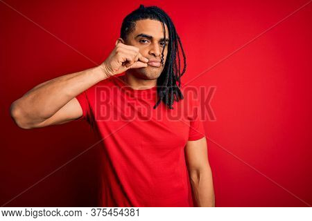 Young handsome african american afro man with dreadlocks wearing red casual t-shirt mouth and lips shut as zip with fingers. Secret and silent, taboo talking