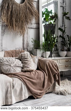 Vertical Photo Of Cozy Lounge Room Interior In Boho Chic Style With Couch, Pillows, Soft Plaid, Hous
