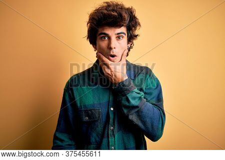 Young handsome man wearing casual shirt standing over isolated yellow background Looking fascinated with disbelief, surprise and amazed expression with hands on chin
