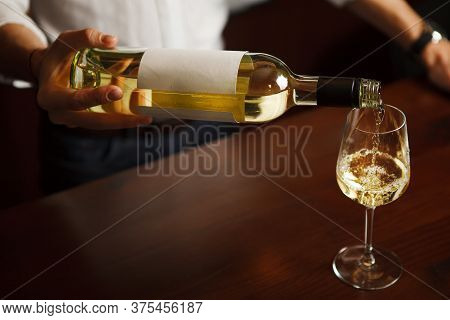Sommelier Working Pouring Fine Alcohol In Glass