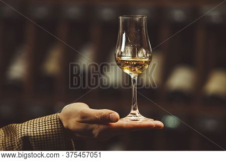 Close-up Photo, Snifter Of Whiskey In Sommelier Hand On Cellar Background.