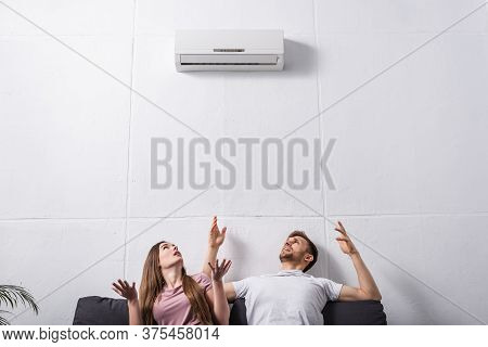 Irritated Couple Suffering From Heat At Home With Broken Air Conditioner
