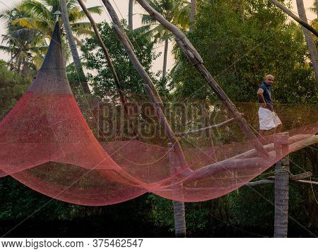 Eramalloor, India - 6 Feb 2017: A Traditional Chinese Fishing Net Is Raised In The Sunset On A Lake,