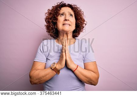 Middle age beautiful curly hair woman wearing casual t-shirt over isolated pink background begging and praying with hands together with hope expression on face very emotional and worried. Begging.