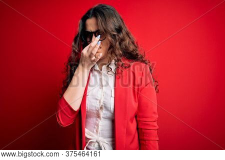 Young beautiful woman with curly hair wearing jacket and glasses over red background smelling something stinky and disgusting, intolerable smell, holding breath with fingers on nose. Bad smell