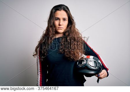 Beautiful motorcyclist woman with curly hair holding moto helmet over white background with a confident expression on smart face thinking serious