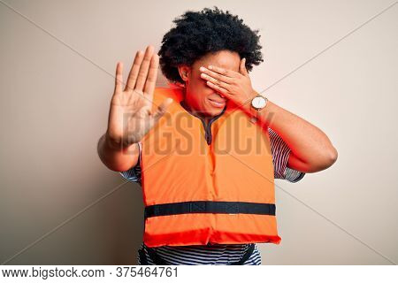 Young African American afro woman with curly hair wearing orange protection lifejacket covering eyes with hands and doing stop gesture with sad and fear expression. Embarrassed and negative concept.