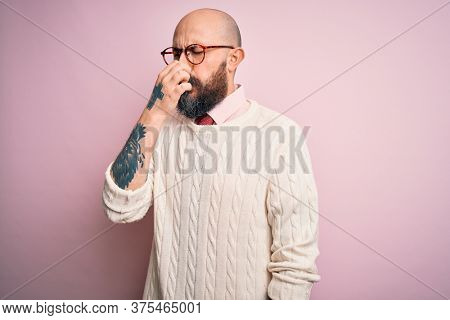 Handsome bald man with beard and tattoo wearing glasses and sweater over pink background smelling something stinky and disgusting, intolerable smell, holding breath with fingers on nose. Bad smell
