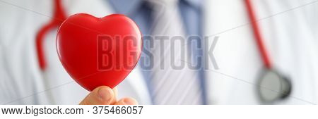 Male Medicine Doctor Hands Holding And Covering Red Toy Heart Closeup. Cardio Therapeutist Student E