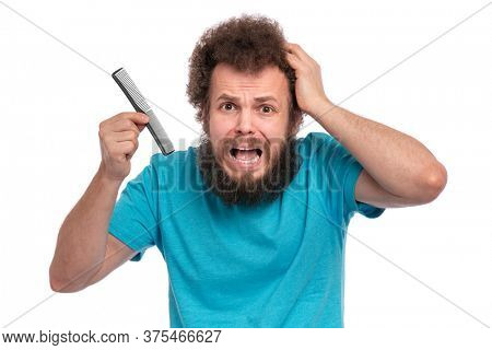 Crazy bearded Man with funny Curly Hair tries to comb his tangled and naughty hair with a small black hairbrush. Shocked face of guy who holds comb, isolated on white background.