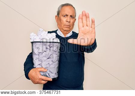 Senior grey-haired man holding full paper bin with crumpled papers over white background with open hand doing stop sign with serious and confident expression, defense gesture