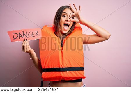 Young beautiful brunette woman wearing lifejacket holding paper with danger message with happy face smiling doing ok sign with hand on eye looking through fingers