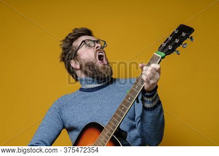 Hipster In An Old Sweater Plays An Acoustic Guitar And Sings Loudly, On A Yellow Background. Hobbies