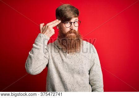 Handsome Irish redhead man with beard wearing casual sweater and glasses over red background Shooting and killing oneself pointing hand and fingers to head like gun, suicide gesture.