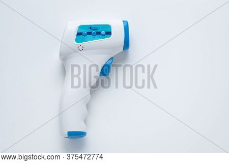 Non-contact Infrared Digital Thermometer On A White Background. Mockup With Copy Space. A Tool For M