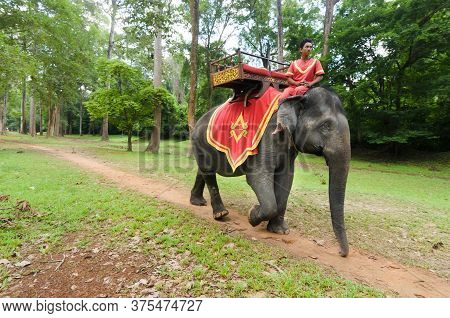 Angkor Wat, Cambodia -5 May 2014: A Young Mahout Is Riding An Asian Elephant Along The Alleyways Of