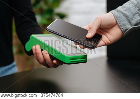 Closeup Of Man\'s Hand With Smartphone Near Nfc Terminal On Counter In Store. Customer Using Smartph